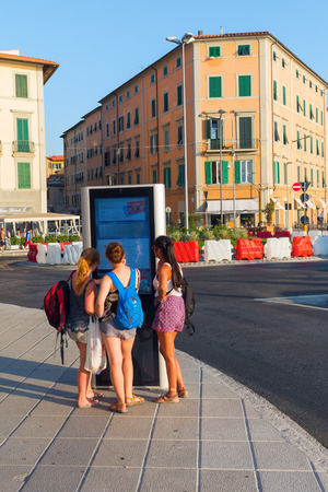 seaports: Livorno, Italy - July 01, 2016: unidentified young women at a digital information board in Livorno. Livorno is a port city on the Ligurian Sea with one of the largest seaports in the Mediterranean Sea Editorial