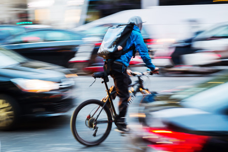 picture of a bicycle messenger in busy city traffic with camera made motion blur effect