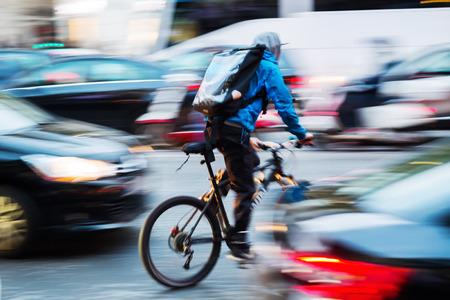 Foto van een fietsboodschapper in drukke stadsverkeer met camera bewegend vervagen effect Stockfoto