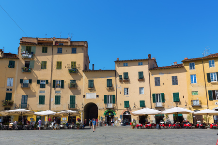 Lucca, Italy, - July 01, 2016: Piazza del Anfiteatro with unidentified people. The ring of buildings surrounding the square, follows the shape of the former 2nd century Roman Amphitheater of Lucca
