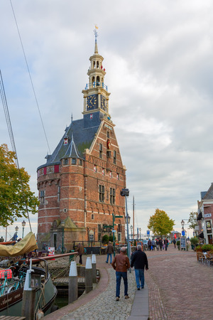12th century: Hoorn, Netherlands - October 08, 2016: Hoofdtoren -main tower- in the harbor of Hoorn, with unidentified people. Hoorn is a harbor town at the Markermeer, dating back to the 12th century