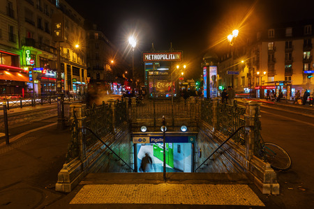 france station: Paris, France - October 20, 2016: Place Pigalle with unidentified people at night. Square and surrounding streets were at the end of 19th century a neighbourhood of painters studios and literary cafes