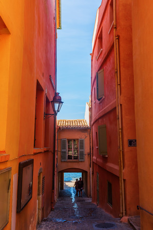 Saint Tropez, France - August 03, 2016: narrow alley to the beach Saint Tropez with unidentified people. St Tropez is a seaside resort at the Cote dAzur, popular for the European and American jet set
