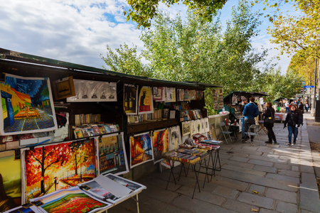 Paris, France - October 19, 2016: Bouquinistes of Paris with unidentified people. They are booksellers of used and antiquarian books who ply their trade along large sections of the banks of the Seine