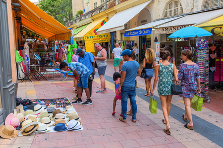 menton: Menton, France - July 30, 2016: shopping street in Menton with unidentified people. The old town with pastel colored facades has an Italian flair and the city is famous for its numerous gardens