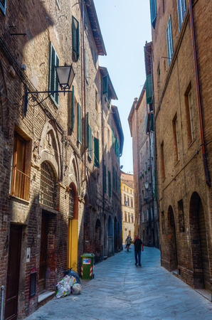 Siena, Italy - July 07, 2016: street scene in Siena with unidentified people. Siena is one of the nations most visited tourist attractions, the old town is declared as UNESCO world heritage site