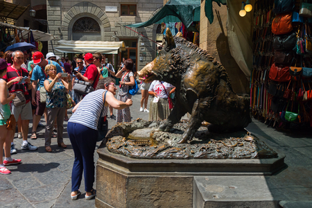 gaping: Florence, Italy - July 06, 2016: bronze fountain of a boar named Il Procellino with unidentified people. Its a popular attraction, visitors put a coin into the boars gaping jaws for having luck Editorial