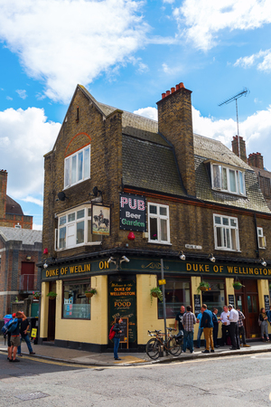 poorer: London, UK - June 16, 2016: old pub with unidentified people in Shoreditch, London. Shoreditch is a inner city district of London. It was one of the poorer districts but today very trendy.