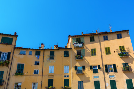 facades of old buildings at the Piazza dell Anfiteatro in Lucca, Italy