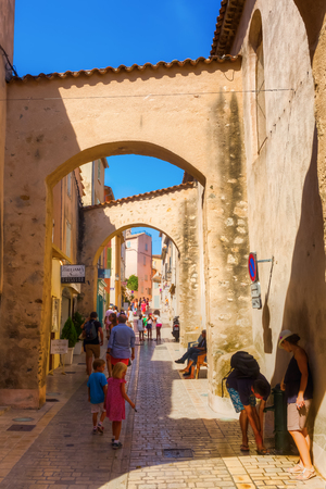 tropez: Saint Tropez, France - August 03, 2016: unidentified people on a picturesque alley in Saint Tropez. St Tropez is a seaside resort at the Cote dAzur and popular for the European and American jet set