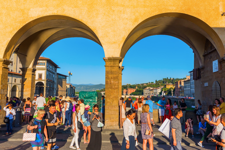 Florence, Italy - July 03, 2016: Ponte Vecchio with unidentified people. It is a Medieval arch bridge over the Arno River, with shops built along it, today jewelers, art dealers and souvenir sellers