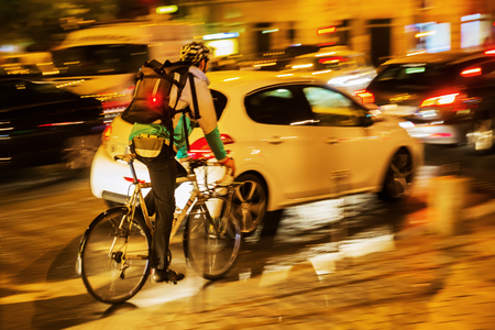 picture of a bicycle messenger in city traffic at night Imagens