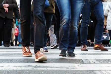 crossing legs: legs of people crossing a street in the city