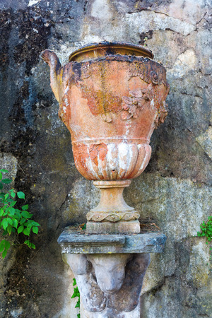 picture of an antique earthenware amphora in front of a decayed wall