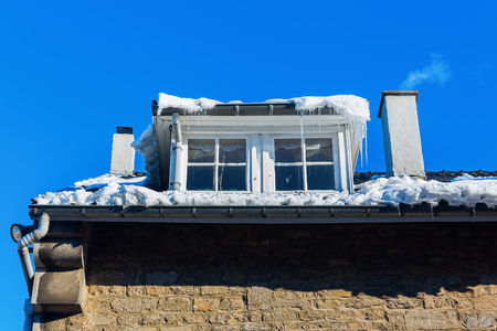 dormer: old building with dormer windows and icicles in winter