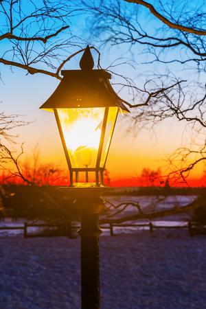 illuminated old street lamp in winter landscape at night