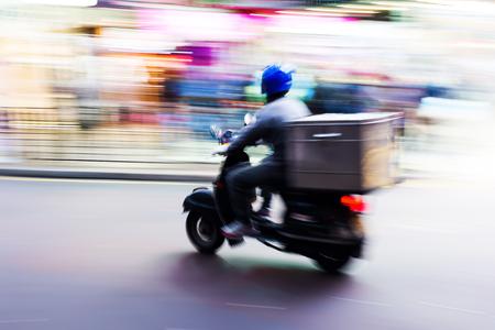 モーションでは、道路上のスクーターのメッセンジャーの画像のぼかし