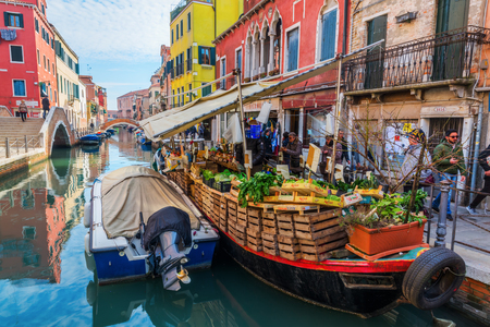 Venice, Italy - February 27, 2017: canal with a market boat in Venice and unidentified people. Venice is world renown for the beauty of its settings.