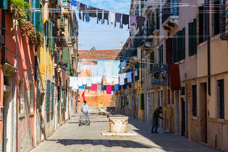 spanned: Venice, Italy - February 27, 2017: typical alley with clotheslines and unidentified people. Venice is world renown for the beauty of its settings.