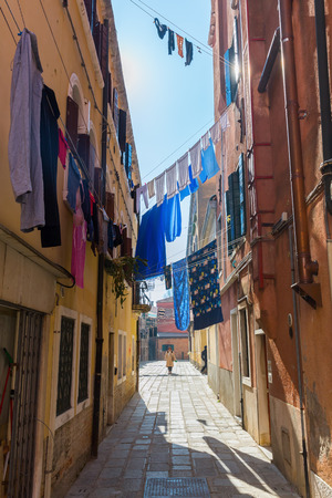 spanned: Venice, Italy - February 27, 2017: typical alley with clotheslines and unidentified people. Venice is world renown for the beauty of its settings Editorial