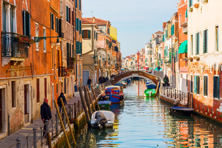 Venice, Italy - February 27, 2017: picturesque canal in Venice with unidentified people. Venice is world renown for the beauty of its settings