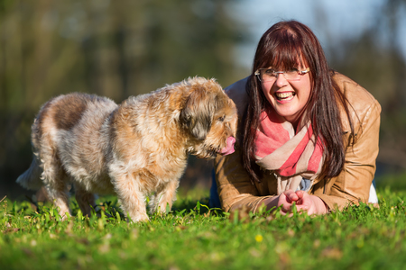 portrait of a young woman lying with her dog in the grass Stock Photo