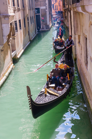 Venice, Italy - February 26, 2017: typical canal with gondola and unidentified people. Venice is world renown for the beauty of its settings