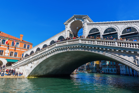 Venice, Italy - February 25, 2017: Rialto Bridge with unidentified people. It is one of the four bridges spanning the Grand Canal, its the oldest and one of the top tourism attractions in Venice