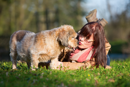 portrait of a young woman lying with her dog in the grass Editorial