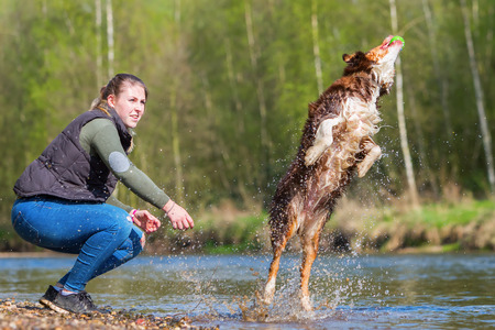 picture of a young woman playing with a dog at the river