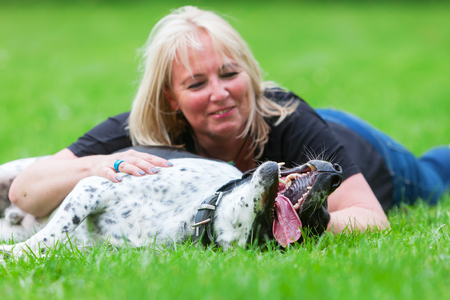 ruffle: portrait of a woman hugging her mixed breed dog on the meadow Stock Photo