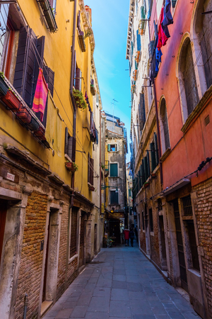 Venice, Italy - February 25, 2017: typical alleyway in Venice with unidentified people. Venice is world renown for the beauty of its settings, a part is listed under UNESCO world heritage sites