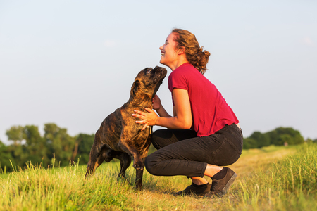 teenage girl playing with a boxer dog in the field