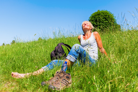 mature woman sitting in a meadow at a hiking rest