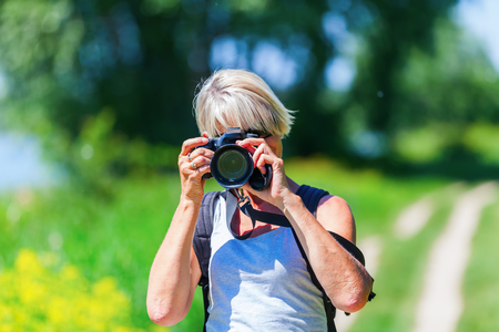 mature woman taking photos with a camera during a hiking trip Standard-Bild