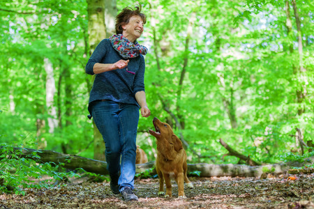 mature woman with her Nova Scota Duck Tolling Retriever in the forest
