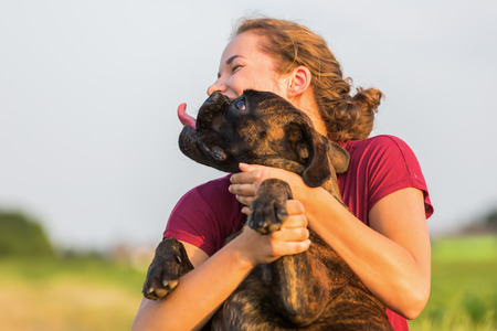 fondling: picture of a young girl who is hugging her boxer dog