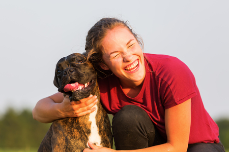 picture of a young girl who is hugging her boxer dog