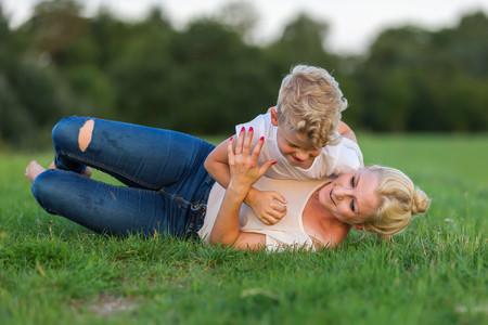 romp: picture of a woman who romps with her son on the grass