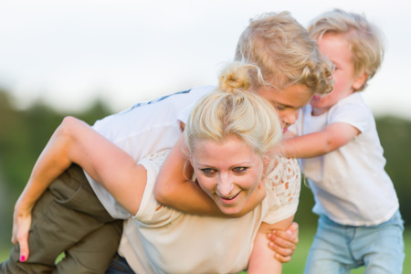 picture of a woman who romps with her two sons on the grass Stock Photo