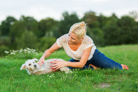 picture of a woman who plays with a terrier hybrid outdoors Stock Photo