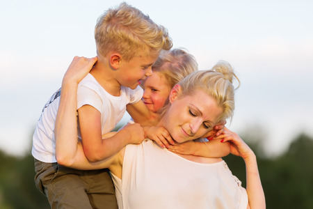 rollick: picture of a woman who romps with her two sons on the grass Stock Photo