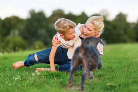 romp: picture of a woman who romps with her son and a dog on the grass
