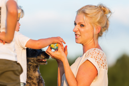 picture of a woman who plays with her boy childs and a dog outdoors