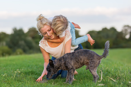 rollick: woman plays with her son and two small dogs on a meadow