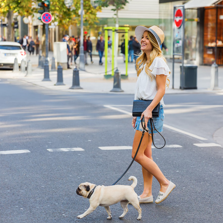 attractive young woman crosses a city street wit a pug at the leash