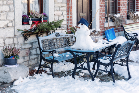 picture of a winter scene with a snowman on a garden table Stock fotó