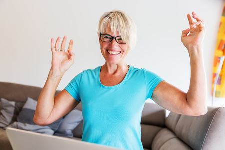 picture of a mature woman sits who is rejoicing with raised hands in front of a laptop
