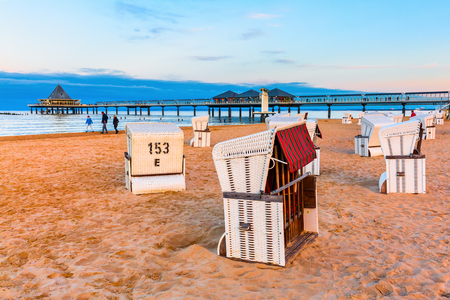 pier of Heringsdorf, Usedom, Germany, with hooded beach chairs in the foreground