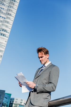 picture of a businessman in the city who reads documents